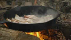 Bacon Frying in a skillet on a fire Stock Footage