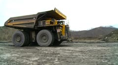 100 ton mining truck moving past camera at surface mining site Stock Footage