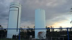 Water Towers Behind Fence Stock Footage