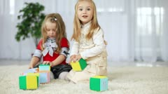 Stock Video Footage of Children play with blocks of tissue. They learn the alphabet sitting on the c