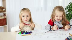 Two girls learn to paint sitting at the table. DOLLY HD Stock Footage