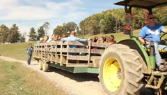 Wagon full of families pulled by tractor Stock Footage