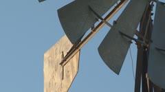 Old metal farm windmill slowly rotates in slight breeze - closeup - stock footage