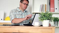 Young man finishing work on laptop and smiling in the office, steadicam shot - stock footage