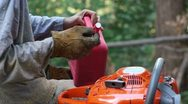 Man puts fuel in chainsaw Stock Footage