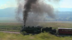 Traveling shot of a steam train moving through the Rocky Mountains. - stock footage