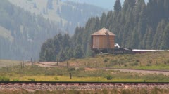 A steam train passes a water tower along the tracks. Stock Footage