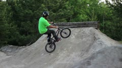Bmx rider doing a downside tailwhip on a dirt obstacle Stock Footage