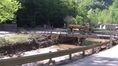 Riding by houses and businesses along creek effected by the flood Stock Footage