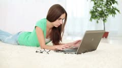 Unhappy girl with laptop lying on the carpet. DOLLY HD Stock Footage