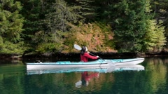 Kayaker paddles past beautiful fall reflection in lake - stock footage