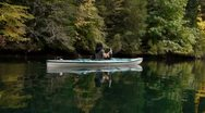 Kayaker paddles through lake with colorful trees 03 Stock Footage