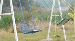 Swinging empty colored swings Stock Footage