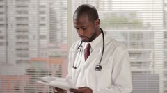 Doctor looking over charts, looking at camera Stock Footage