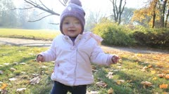 Happy baby learns to walk in a autumn park - stock footage