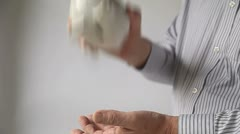Businessman shakes piggy bank Stock Footage
