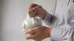 Businessman puts pennies in piggy bank Stock Footage
