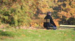 Elderly man sits on a bench in autumn park Stock Footage