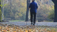 Man nordic walking in autumn park Stock Footage