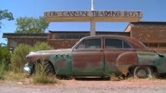 A slow moving shot tracking along an old rusted car at an abandoned trading Stock Footage
