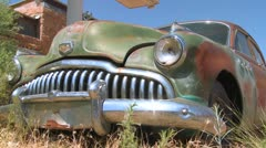 An old rusting car sits abandoned. - stock footage