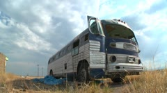 Stock Video Footage of A moving time lapse shot of an abandoned Greyhound bus in a field.