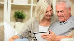 Retired Caucasian Couple Using a Wireless Tablet Stock Footage