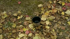 Pour water in mug on falling yellow leaves,travel material. Stock Footage