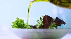 Pouring olive oil onto fresh salad - stock footage
