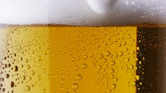 Beer being poured. Foam sliding down side of beer glass Stock Footage