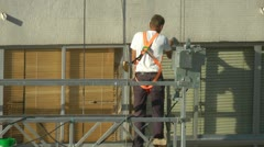 Construction worker on scaffolding repairing the building Stock Footage