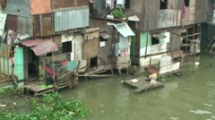 Slum Houses On Bank Of Polluted River Stock Footage