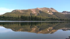 The Rocky Mountains are perfectly reflected in an alpine lake. Stock Footage