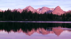 The Rocky Mountains are perfectly reflected in an alpine lake at sunset. - stock footage