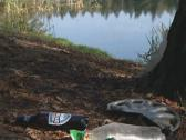 Litter on lake coast and fisherman fishing from boat. Stock Footage