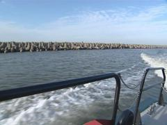 Pier shot from ship passing by. Wave breaker. Stock Footage