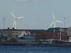 Windmills generating electricity near industrial buildings. Stock Footage