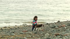 Cute little girl with dog on beach Stock Footage