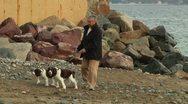 Elderly woman walking dogs on beach Stock Footage