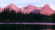 The Rocky Mountains are perfectly reflected in an alpine lake at sunset or dawn. Stock Footage