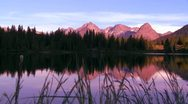 The Rocky Mountains are perfectly reflected in an alpine lake at sunset or dawn Stock Footage