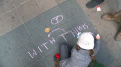 Politics and Protest, Occupy (Wall-Street) Calgary, child drawing with chalk Stock Footage
