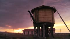 A water towers along an abandoned railroad track at dusk. Stock Footage