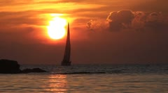 Sailboat passes in front of sun during sunset Stock Footage