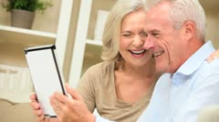 Mature Caucasian Couple Using a Wireless Tablet at Home Stock Footage