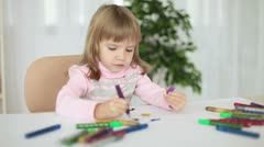 Child draws markers at the table Stock Footage