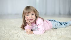 Happy child lying on a carpet. Looking at camera - stock footage