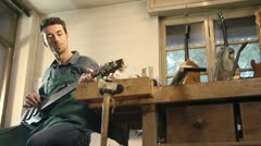 Italian artisan in workshop, playing custom guitar Stock Footage