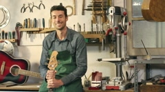 Happy italian artisan at work, smiling in guitar workshop Stock Footage