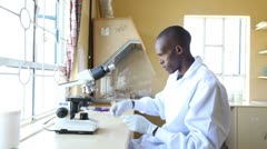 Medical technician using microscope in clinic. Kenya, Africa. Stock Footage